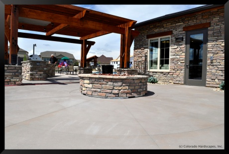 Colored concrete paving with fire pit and polished concrete countertop at the grill by Colorado Hardscapes