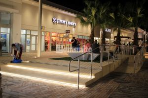 A Bomanite Exposed Aggregate with Seashells step platform and handicap ramp installed by Edwards Concrete Company creates seating and lighting at the Tanger Outlets mall located in Daytona Beach, FL