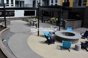 CoLab Cohousing located in Denver, Colorado created a stylish student living community with Bomanite Sandscape Refined installed around the board formed firepit and Bomanite Sandscape Textured Walking Paths
