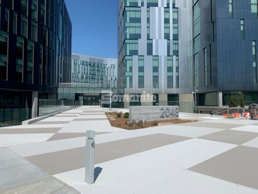The Bomanite Toppings Systems were utilized at the new Cerner campus in Kansas City by Bomanite Licensee Musselman and Hall with an installation of Micro-Top XT in Nickel Gray Integral Color in a broom finish and Micro-Top ST with a French Gray Integral Color spray applied created consistency in application and color and mirrored the window and sheathing pattern on the buildings.