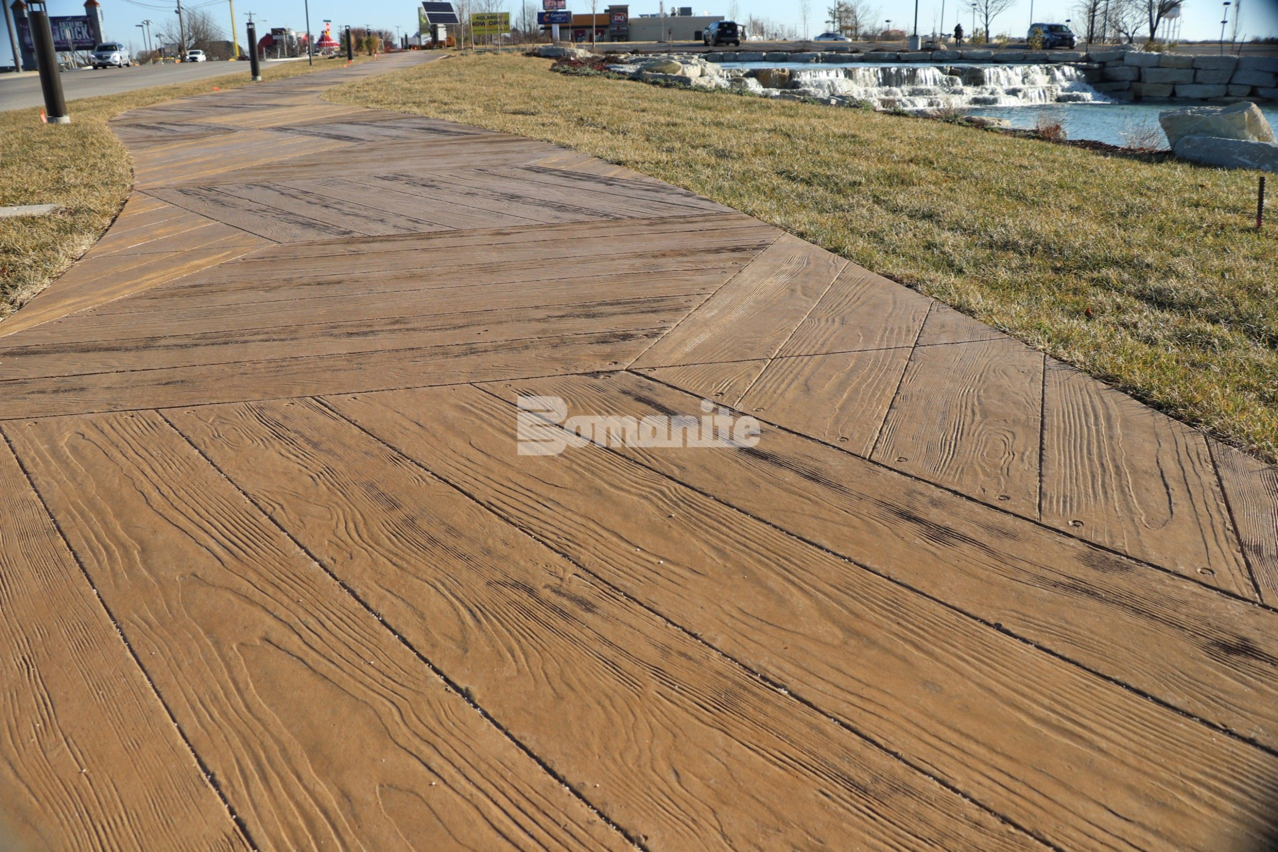 Using the Bomanite Imprint Systems Musselman and Hall Contractors worked with PGAV Destinations in creating a custom Hexagon Boardwalk pattern with Custom Radius Wood Grain Planks that snake around the entrance to the Branson Boardwalk Aquarium.