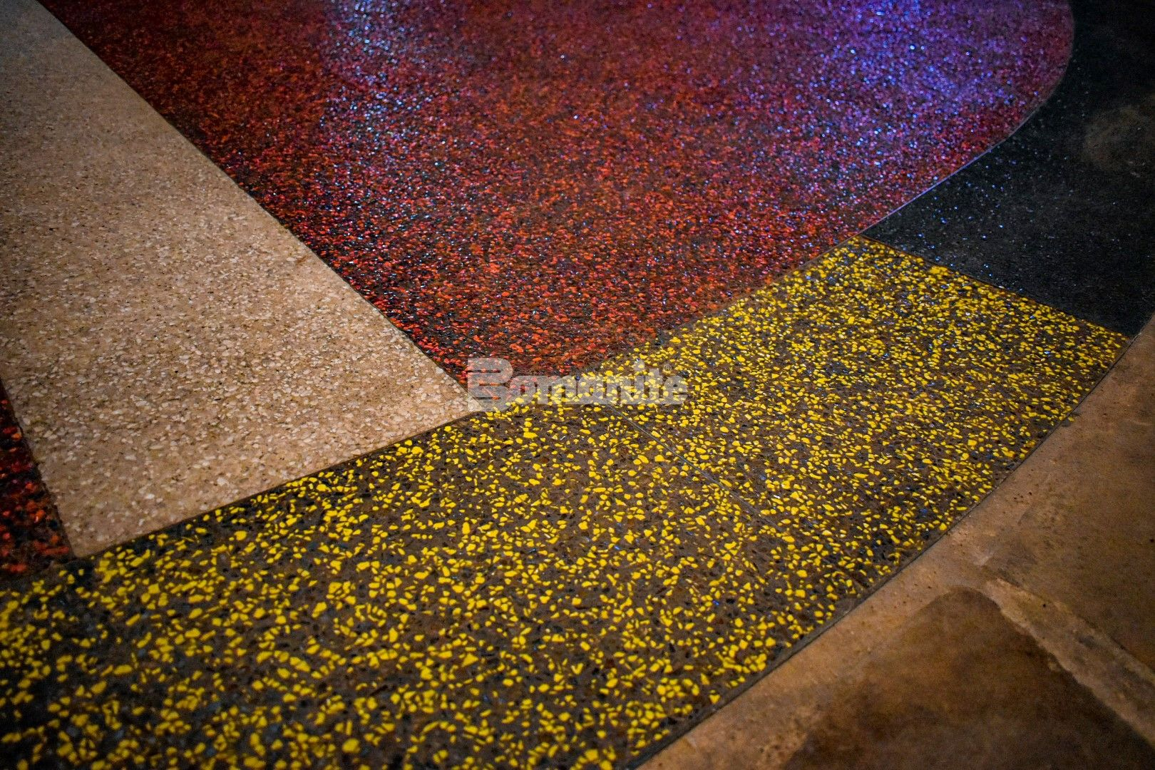 Bomanite Exposed Aggregate Revealed System in White, Red, Yellow and Black showcases the significant diamond symbol to the chata people at the interior entrance of the Choctaw Cultural Center
