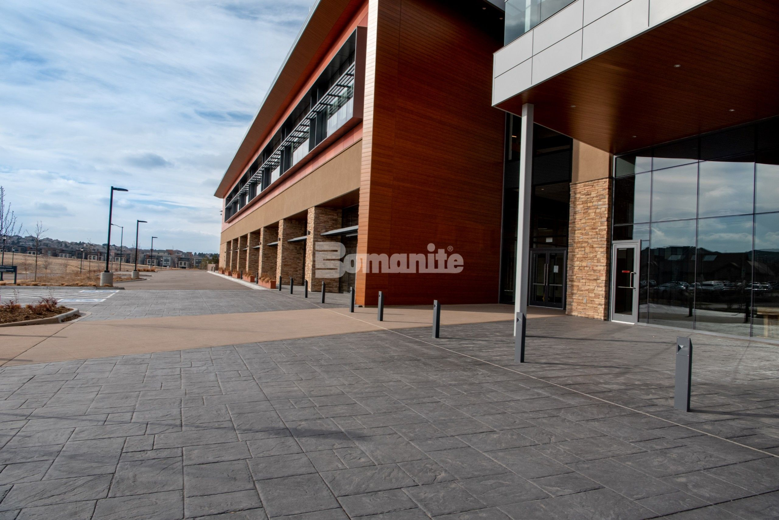 Colorado Hardscapes Installs Award Winning Bomanite Decorative Concrete Details for The Charles Schwab Conference Center at Ridgegate with a mix of Gray Bomanite Imprinted concrete systems for the field and Bomanite Exposed Aggregate Systems Sandscape Texture for accentuated bands of color.